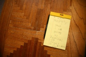 "Yellow Notepad on Wooden Desk with Child's Writing Starting with ""I am Happy"""