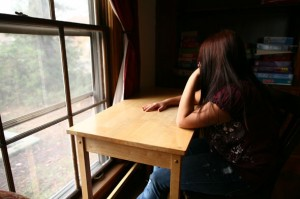 Sad Young Teenage Girl Sitting at a Desk Looking out a Window